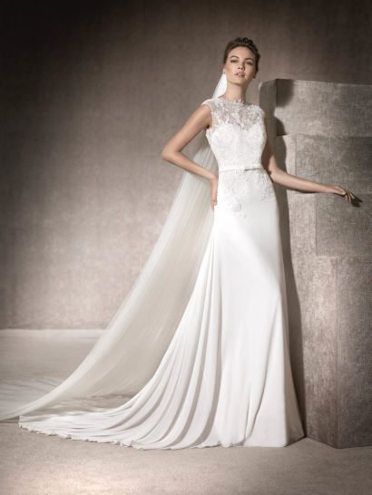 Романтичное свадебное платье привлекает взгляды изящной прямой юбкой, чуть расклешенной снизу и дополненной торжественным шлейфом из тонкой ткани.  Корсет с лифом в форме сердечка покрыт шантильским кружевом и вышивкой бисером, на линии талии располагается узкий пояс с маленьким бантом спереди.  Открытая корсетом спинка смотрится деликатно и изящно, она покрыта кружевной вставкой с бисерным декором.