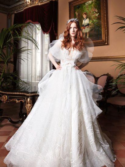 Роскошное свадебное платье дополнено эффектным полупрозрачным болеро с объемными рукавами.  Открытый корсет с жесткими косточками великолепно сочетается с драматичной пышной юбкой из кружева, тюля и органзы.  Такой образ великолепно подойдет невесте, мечтающей о классике с нотами экстравагантной современности.  Дополнить платье можно выразительным поясом от YolanCris.  Свадебные платья Yolan Crisэксклюзивно представлены в салоне Виктория  Примерка платьев Yolan Cris —платная