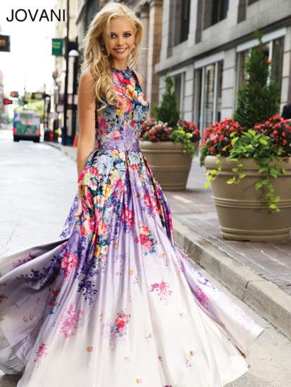 Очаровательное вечернее платье в бело-лиловых тонах выполнено из эффектной атласной ткани с плотным цветочным узором.  Округлый вырез красиво очерчивает шею.  На спине располагается стильный вырез «замочная скважина».  Длинная торжественная юбка спускается множеством объемных вертикальных складок.  Завершением образа служит небольшой шлейф сзади.
