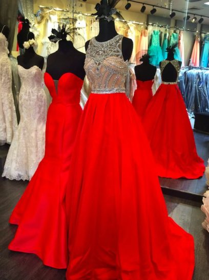 Великолепное вечернее платье с длинной красной юбкой, дополненной небольшим шлейфом.  Открытый корсет с лифом в форме сердечка выполнен из бежевой ткани.  Она покрыта прозрачным верхом, расшитым крупным серебристым бисером по всей длине.  Спереди шею обрисовывает округлый вырез.  Сзади платье украшено эффектным вырезом «замочная скважина».