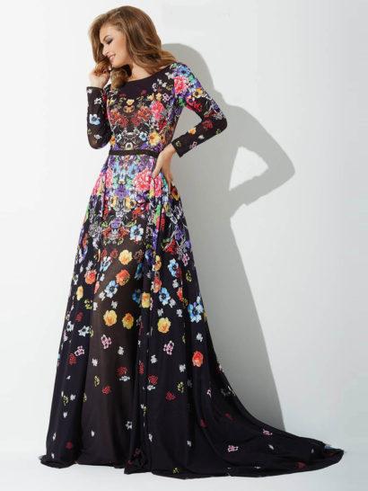 Создайте запоминающийся образ с помощью оригинального вечернего платья.  Черный цвет ткани служит прекрасным фоном для многоцветного цветочного рисунка.  Широкий округлый вырез обнажает плечи, его стильно дополняют длинные облегающие рукава.  Спинка открыта драматичным V-образным вырезом.  От выделенной узким поясом талии спускается юбка А-силуэта с небольшим шлейфом.