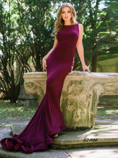 Великолепное вечернее платье глубокого винного оттенка изящно обрисовывает фигуру – ваш образ будет самым эффектным на торжественном мероприятии!  Лаконичный вырез бато красиво очерчивает шею и драматично сочетается с глубокими вырезами по бокам.  Для комфорта движений вырезы оформлены тонкой тканью.  Особым украшением платья является длинный шлейф, спускающийся легкими волнами ткани.