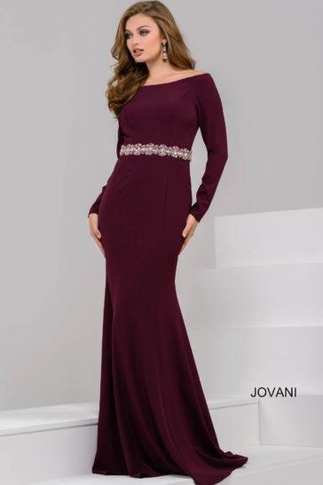Бордовое вечернее платье облегающего кроя со сверкающим поясом и открытыми плечами.