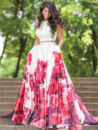Впечатляющее вечернее платье белого цвета дополнено крупным цветочным принтом в красно-черных тонах.  Эффектные бутоны прекрасно дополняют длинную юбку А-силуэта со скрытыми карманами.  Укороченный топ оригинального кроя соблазнительно обнажает область талии и красиво подчеркивает открытые плечи.