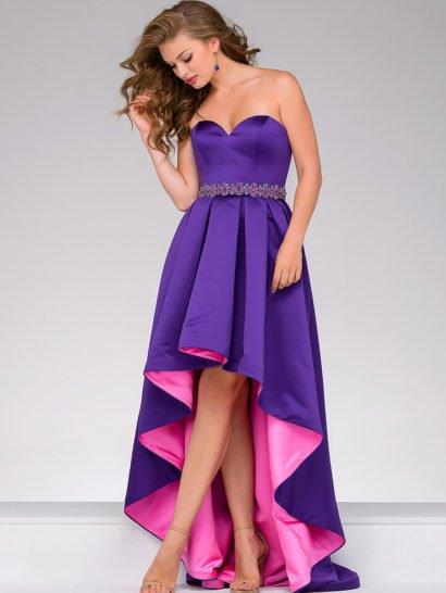 Атласное вечернее платье фиолетового цвета очаровывает яркой розовой подкладкой, которая становится выразительным акцентом благодаря укороченному спереди подолу. Открытый лиф в форме сердечка безупречно обрисовывает область декольте. Длинный шлейф сзади красиво дополняет образ, как и сияющий пояс на талии, украшенный бисером и стразами по всей длине.