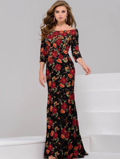 Стильное вечернее платье облегающего фигуру кроя, покрытое по всей длине выразительным рисунком с яркими красными бутонами роз по темному фону.  Округлое декольте, открывающее плечи, очень женственно смотрится в сочетании с изящным рукавом длиной три четверти.  Юбка создает легкие складки ниже середины бедра, что делает образ эффектнее и обеспечивает комфорт движений.