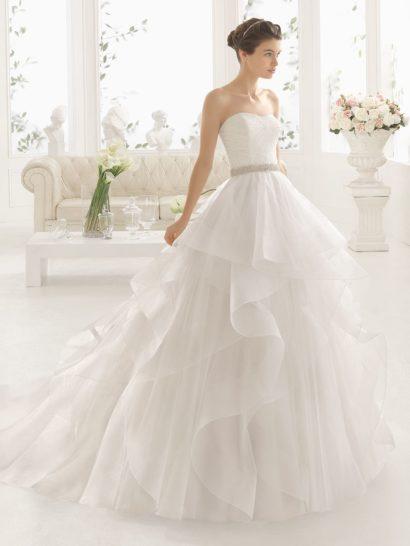 Потрясающее свадебное платье создано для самых романтичных и нежных невест.  Его пышную юбку создает несколько причудливых ярусов полупрозрачной ткани.  Сзади юбка деликатно переходит в шлейф.  Лаконичность лифа уравновешивает драматичную красоту подола.  Декольте подчеркивает фигуру, как и широкий сверкающий пояс на талии.