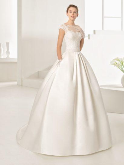 Великолепное свадебное платье пышного кроя приковывает взгляды благородным глянцем атласной юбки.  Дополняют ее скрытые карманы, придающие изюминку торжественному образу.  Декольте сердечком укрыто плотной кружевной тканью, она же располагается и над вырезом на спинке.  На талии пояс, украшенный сзади объемным бантом.