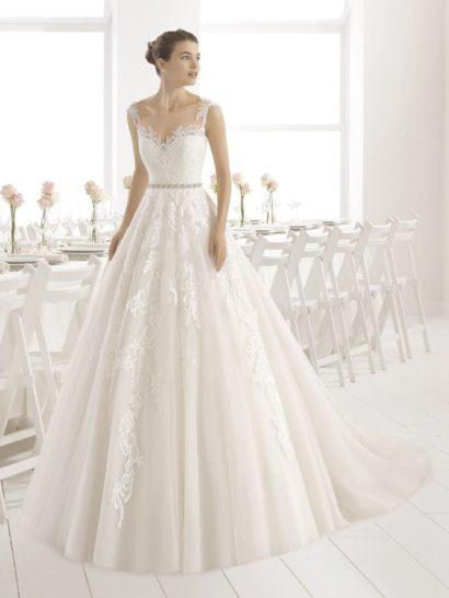 Деликатное свадебное платье - для нежной и мечтательной невесты.  Ключевым элементом образа является кружево, не только придающее воздушность юбке, но и оформляющее тонкую вставку над лифом.  Растительный узор создает фигурные бретели.  Талию сдержанно очерчивает узкий пояс, покрытый серебристым бисером.  Небольшой шлейф становится идеальным завершением утонченного образа.