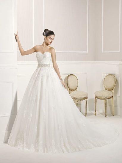 В открытом свадебном платье А-силуэта вы очаруете всех красотой и женственностью.  Это идеальный выбор для традиционного романтичного торжества.  Корсет с лифом в форме сердца покрыт кружевной отделкой, оттеняющей серебристый пояс с бисером.  Многослойная юбка оформлена аппликациями, вертикальными складками ткани и пышным шлейфом.