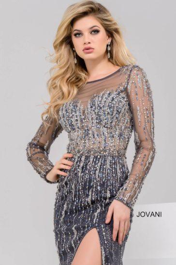 Серое вечернее платье с длинным рукавом из тонкой ткани и разрезом сбоку на юбке.