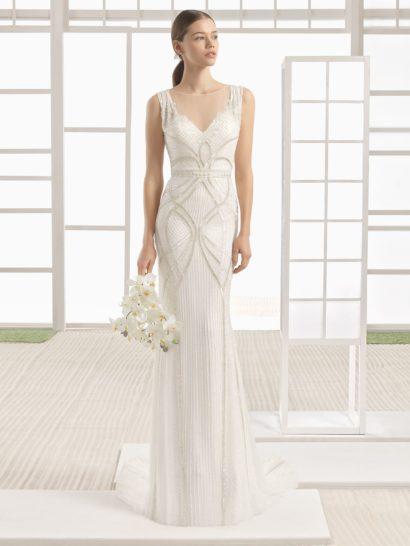 Утонченные линии прямого свадебного платья покорят невест, предпочитающих сдержанный стиль.  Легкая плиссировка придает выразительность лаконичной юбке, а выше силуэт украшают эффектные изгибы фактурного декора.  Линия талии очерчена поясом. Изящный вырез сердечком дополняют широкие симметричные бретели и элегантная вставка из полупрозрачной ткани.