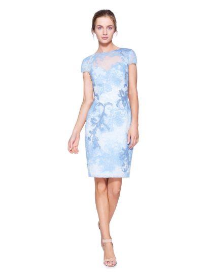 Элегантное коктейльное платье-футляр выполнено в освежающих тонах белого и голубого. Сдержанный крой с округлым вырезом под горлом, закрытой спинкой и коротким прямым рукавом выглядит достаточно женственно и красиво обрисовывает фигуру.  Полупрозрачная вставка над декольте и крупные ажурные изгибы отделки наполняют настроение образа нежностью и романтикой.