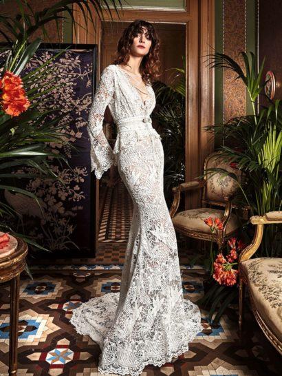 """Крайне актуальное свадебное платье выполнено в стиле """"бохо"""".  Облегающий силуэт «русалка» сочетается с рукавами-колокольчиками.  Платье выполнено из очаровательного фактурного гипюра.  Стоит также обратить внимание на великолепную отделку корсета и на изысканный округлый шлейф, простирающийся за юбкой сзади."""