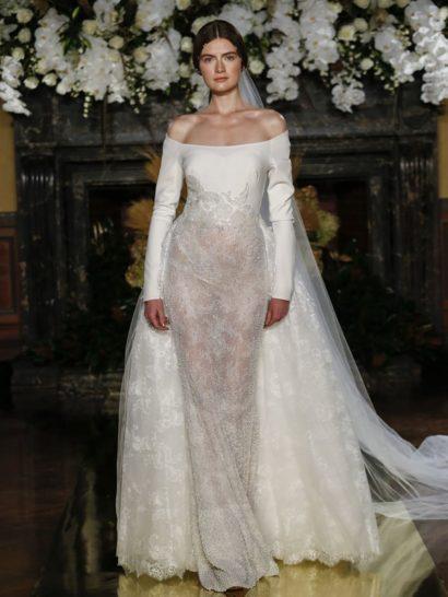 Элегантное свадебное платье с длинным рукавом и силуэтом «русалка» привлекает сдержанной линией декольте «бато».  Корсет создан из плотного крепа, который контрастно сочетается с юбкой из французского кружева.  Великолепным дополнением образа становится роскошная фата – она оформлена таким же кружевом, как и чарующая юбка.