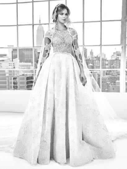 Фактурное свадебное платье очаровывает царственной юбкой «принцесса».  Открытый лиф в форме «сердечка» покрыт кружевной тканью, создающей короткие рукава и фигурный вырез под горло.  Многослойная юбка с длинным шлейфом от талии до низа подола покрыта мелким кружевным узором.  Край юбки кружево делает фигурным.    В НАЛИЧИИ