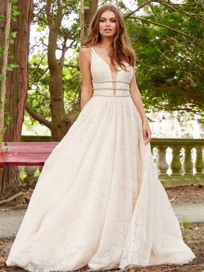 Очаровательное вечернее платье оттенка шампанского, декорированное фактурной вышивкой по всей длине. Глубокий V-образный вырез обрамлен тонкими бретелями. Область талии выделена двумя узкими поясами. Сзади платье открыто глубоким вырезом. Юбку украшают нежные вертикальные складки.