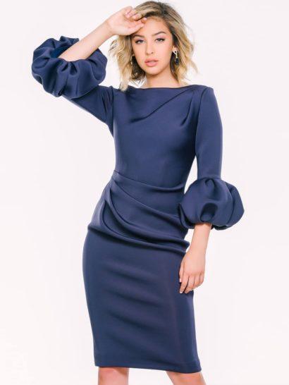 Оригинальное и изысканное вечернее платье темно-синего цвета соответствует даже самому торжественному празднику. При этом, образ удивительно лаконичный.  Рукава в три четверти дополнены объемными воланами. Закрытый верх очерчивает линию шеи женственным вырезом «лодочка».