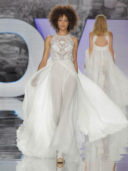 Оригинальное свадебное платье в богемном стиле, складывающееся из двух элементов.  Дополненный тюлем верх украшен вышивкой с цветочными мотивами и деликатными стразами.  Шифоновая юбка наполнена легкостью и динамизмом.  Контраст текстур и форм создает идеальный для богемной невесты силуэт.