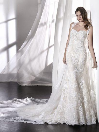 Элегантное свадебное платье «русалка» с заниженной талией, в котором открытый вырез «сердечком» сочетается с открытой спинкой.  Наряд оформлен тюлем, покрытым вышивкой, и кружевными аппликациями с бисером.  Это очень романтичное платье, которое можно дополнить роскошным съемным кейпом из тюля и кружева, таких же, как и сам наряд.