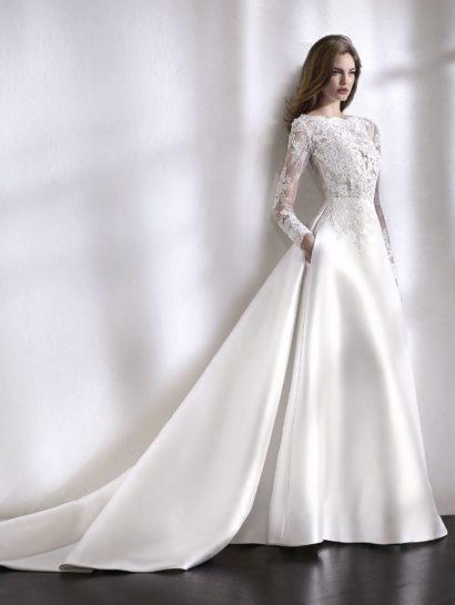 Утонченное и очень изысканное свадебное платье с бальным силуэтом покоряет юбкой из шелка микадо и верхом, созданным из тюля с вышивкой и кружева шантильи с бисером.  Детали образа представляют элегантную игру контрастов.  Полупрозрачный верх с длинным рукавом красиво дополняет классическую ткань юбки.  К платью прилагается съемная подкладка для верха.