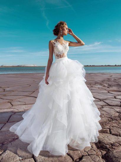 Великолепное свадебное платье объединяет в одном образе актуальную иллюзию прозрачности и традиционную пышность, которая никогда не теряет привлекательности.  Многослойная юбка покрыта оборками по всей длине, что контрастно смотрится с облегающим фигуру верхом.  При желании, ее можно снять – получится стильное платье-футляр с юбкой до колена, безупречно акцентирующей силуэт.