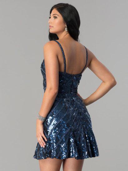 Смелый вечерний образ обеспечивает платье с юбкой до середины бедра. Стильный характер платья поддерживает и открытый лиф «сердечком» на бретельках-спагетти. По всей длине вечернее платье покрыто сияющей вышивкой из пайеток. Темно-синий оттенок платья делает такую отделку впечатляюще красивой.