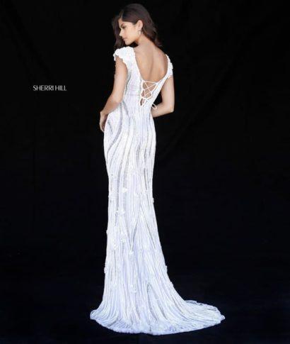 Белое вечернее платье облегающего кроя, украшенное вышивкой.