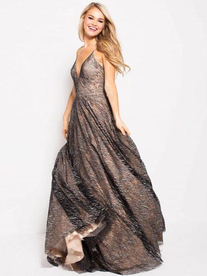 Необычное вечернее платье подарит особенные эмоции на выпускном вечере. Темно-серый сияющий верх из полупрозрачной ткани с деликатным рисунком. дополняет кремовую подкладку по всей длине. Верх на тонких бретелях акцентирует декольте и полностью открывает спинку. От самой линии талии сзади спускается небольшой пышный шлейф.