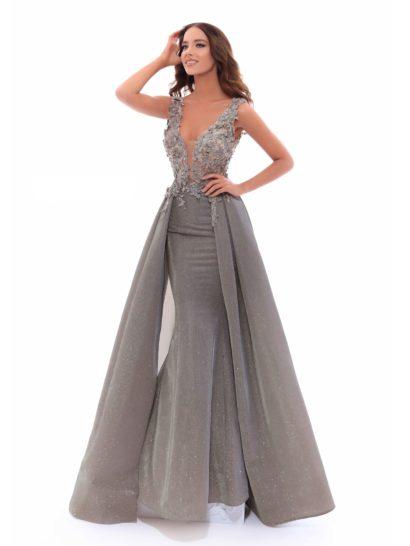 Великолепное серое вечернее платье притягивает внимание кроем юбки в пол. Ее облегающий силуэт дополнен пышным верхом, спускающимся роскошными вертикальными складками сзади. Глубокий V-образный вырез лифа дополнен тонкой вставкой. Верх декорирован объемными аппликациями, привносящими в образ романтичное настроение.