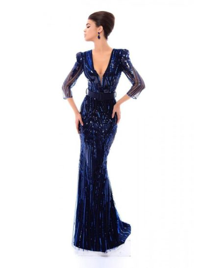 Облегающее вечернее платье сразу же притягивает внимание глубоким оттенком синего. Драматичный V-образный вырез с тонкой вставкой стильно сочетается с прямыми рукавами длиной в три четверти. Подчеркнуть талию позволяет широкий матовый пояс. По всей длине вечернее платье покрыто сияющей отделкой пайетками в тон ткани.