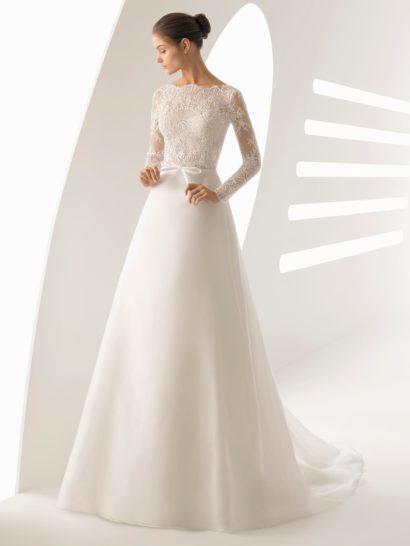 Женственное свадебное платье является прекрасным воплощением силуэта «принцесса».  Лаконичная юбка переходит в шлейф от самой линии талии, выделенной узким поясом.  Верх платья украшен кружевом, создающим облегающие длинные рукава и фигурный вырез под горло.  Сзади тонкая ткань очерчивает чувственный V-образный вырез.