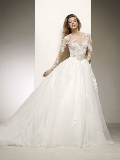 Торжественное свадебное платье с многослойной юбкой выглядит невероятно романтично и нежно.  Облегающий корсет с лифом «сердечком» оформлен с иллюзией прозрачности и дополнен длинным рукавом.  Роскошный подол юбки с длинным шлейфом декорирован небольшими аппликациями, которые подчеркивают объем силуэта.