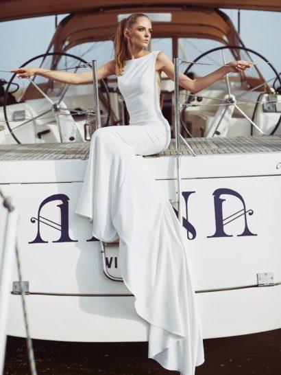 Лаконичное свадебное платье облегающего силуэта впечатляет изысканной спинкой с глубоким округлым декольте.  Оно декорировано прозрачной вставкой, покрытой сногсшибательным вышитым узором.  Спереди лиф очень сдержанный, с широкими бретелями и вырезом «лодочкой».  Завершением образа служит шлейф, спускающийся от уровня коленей.
