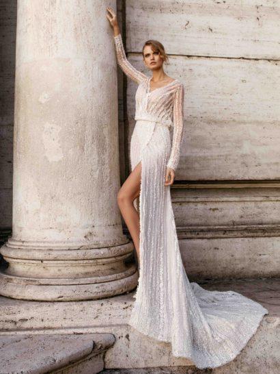 Станьте центром всеобщего внимания в драматичном свадебном платье прямого силуэта, украшенном чарующим шлейфом.  Эффектный разрез высоко по подолу и глубокое декольте – безупречная комбинация, позволяющая подчеркнуть фигуру.  На спинке располагается необычный вырез «замочная скважина», обрамленный тонкой фактурной тканью.