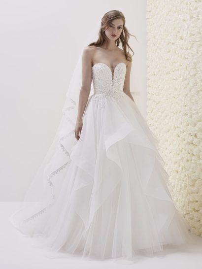 Оригинальное и романтичное свадебное платье с многослойной пышной юбкой, украшенной объемными полупрозрачными воланами.  Фактурный кружевной корсет с головокружительно глубоким вырезом прекрасно подчеркивает область декольте, дополняет вырез прозрачная вставка.  Сзади платье декорировано шлейфом, линии которого подчеркнуты воланами.
