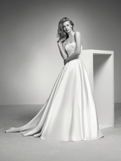 Эффектное свадебное платье создано из роскошного шелка микадо, наполняющего сиянием и без того выразительный пышный силуэт.  Это идеальный образ для ценительницы классики.  Лаконичный открытый лиф, подчеркивающий линию плеч, полностью покрыт бисерной вышивкой.  Она контрастно сочетается с юбкой без отделки, спускающейся объемными вертикальными складками и образующей сзади шлейф.